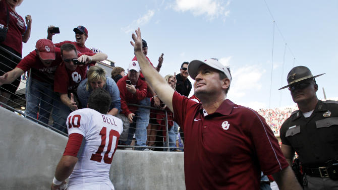 Oklahoma's Blake Bell (10) and head coach Bob Stoops, center, acknowledge fans as they leave the field following an NCAA college football game against TCU Saturday, Dec. 1, 2012, in Fort Worth, Texas. Oklahoma won 24-17. (AP Photo/Tony Gutierrez)
