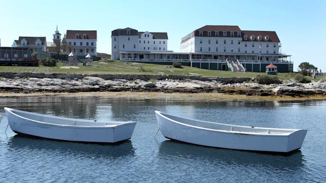 In this photo taken Friday, Sept. 14, 2012, dories float in the bay in front of the historic Star Island Family Retreat and Conference Center, and the Oceanic Hotel, far right, at the Isle of Shoals in Rye, N.H. The hotel, 10 miles off the coast of New Hampshire, wants to establish itself as an environmental leader. The island is essentially a self-contained system, and it is an ideal spot to showcase energy innovations and could be become a model for other communities. (AP Photo/Jim Cole)