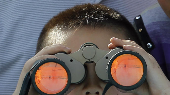 A child uses a pair of binoculars to view the  Shenzhou 9 spacecraft rocket before it launches from the Jiuquan Satellite Launch Center in Jiuquan, China, Saturday, June 16, 2012. China sends its first woman and two other astronauts into space Saturday to work on a temporary space station for about a week, in a key step toward becoming only the third nation to set up a permanent base in orbit.(AP Photo/Ng Han Guan)