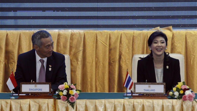 Singapore's Prime Minister Lee Hsien Loong, left, sits next to Thailand's Prime Minister Yingluck Shinawatra during the singing ceremony of adoption of the ASEAN Human Rights Declaration during the 21st Association of Southeast Asian Nations, or ASEAN Summit in Phnom Penh, Cambodia, Sunday, Nov. 18, 2012. (AP Photo/Vincent Thian)