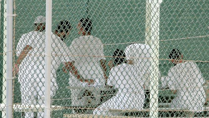 GUANTANAMO BAY, CUBA - AUGUST 23:  Detainees gather in a court yard at Camp Delta at Guantanamo Naval Base August 23, 2004 in Guantanamo, Cuba. On August 24, preliminary hearings will begin for four suspected Al Qaeda associates charged by the U.S. with war crimes as they appear before a commission of five military officers.  (Photo by Mark Wilson/Getty Images)