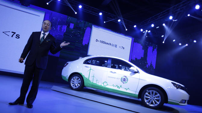 """Geely Holding Group Vice President Feng Qingfeng unveils the Chinese automaker's new electric car """"EC7"""" during a press conference ahead of the Shanghai International Automobile Industry Exhibition (AUTO Shanghai) in Shanghai, China Friday, April 19, 2013. (AP Photo/Eugene Hoshiko)"""