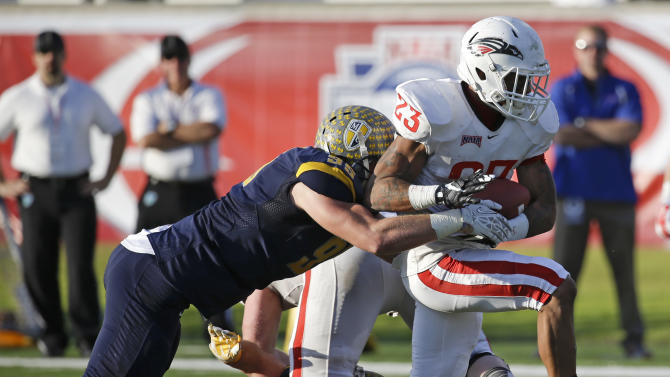 Southern Oregon running back Melvin Mason (23) breaks away from Marian defensive players Donnie Dulaney, left, and Ryan Hartnett (2) for a touchdown during the first half of an NAIA Football National Championship game in Daytona Beach, Fla., Friday, Dec. 19, 2014. (AP Photo/John Raoux)