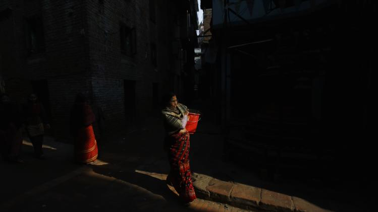 A woman carrying a bucket walks along streets of Lalitpur