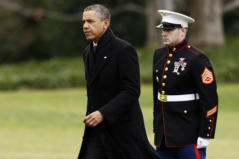 President Barack Obama walks past a Marine honor guard as he steps off the Marine One helicopter and walks on the South Lawn at the White House in Washington, Thursday, Dec. 27, 2012, as he returned early from his Hawaii vacation for meetings on the fiscal cliff. (AP Photo/Charles Dharapak)