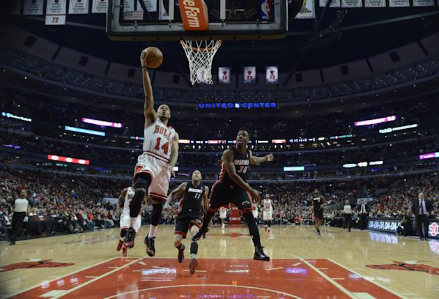 Chicago Bulls' D.J. Augustin (14) goes up to shoot against Miami Heat's Norris Cole (30) during the first quarter of an NBA basketball game in Chicago, Sunday, March 9, 2014. Chicago won 95-88