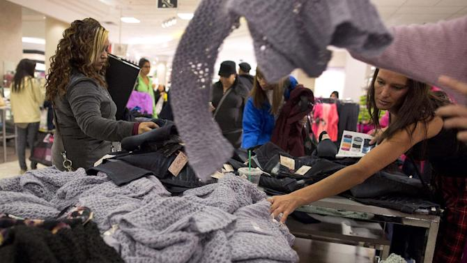 Shoppers rummage through a pile of sweaters on sale at a J.C. Penney store, Friday, Nov. 23, 2012, in Las Vegas. Despite a surge of resistance as the sales drew near, with scolding editorials and protests by retail employees and reminders of frantic tramplings past, Black Friday's grip on America may be stronger than ever. (AP Photo/Julie Jacobson)