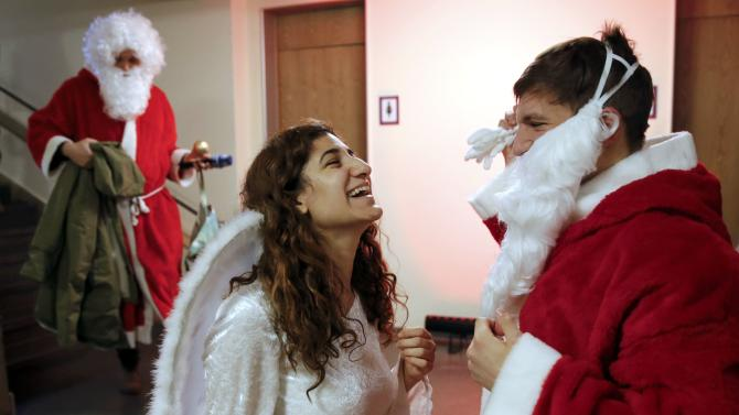 Students dressed as Santa Claus and an angel joke during the annual meeting of the rent-a-Santa Claus service of Berlin's universities in Berlin