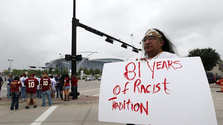 "FILE - In this Oct. 13, 2014 file photo, Juan Mancias, of Floresville, Texas, a member of the American Indian Movement of Central Texas, holds a sign as he joins others in protest before an NFL football game between the Washington Redskins and Dallas Cowboys in Arlington, Texas. The U.S. Patent Office ruled Wednesday, June 18, 2014, that the Washington Redskins nickname is ""disparaging of Native Americans"" and that the team's federal trademarks for the name must be canceled. (AP Photo/Sharon Ellman, File)"