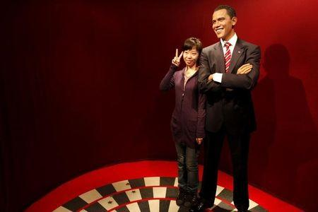 A visitor poses for a photo next to a wax statue of U.S. President Barack Obama at Madam Tussaud's wax museum in Shanghai