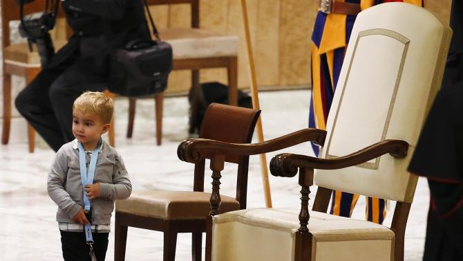 A child wake past Pope Francis' chair during a special audience in Paul VI hall at the Vatican