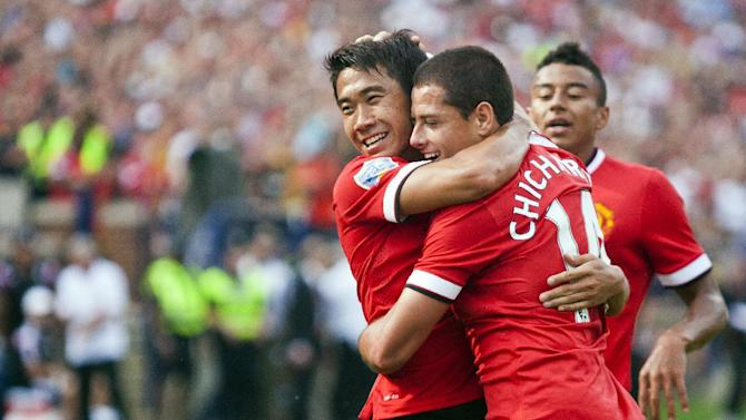 Manchester United midfielder Shinji Kagawa, left, celebrates his assist for a goal from forward Javier Hernandez (14), in the second half of a Guinness International Champions Cup soccer match at Michigan Stadium, Saturday, Aug. 2, 2014, in Ann Arbor, Mich. Manchester United defeated Real Madrid 3-1. (AP Photo/Tony Ding)