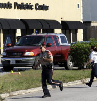 Members of the Montgomery County Sheriff's Department work the crime scene where a mother was killed and her baby was kidnapped Tuesday, April 17, 2012, in Spring, Texas. A newborn boy was abducted from his screaming mother after she was repeatedly shot outside a suburban Houston pediatric center on Tuesday, according to investigators searching for the suspected shooter who sped off with the infant in a blood-stained Lexus. (AP Photo/David J. Phillip)