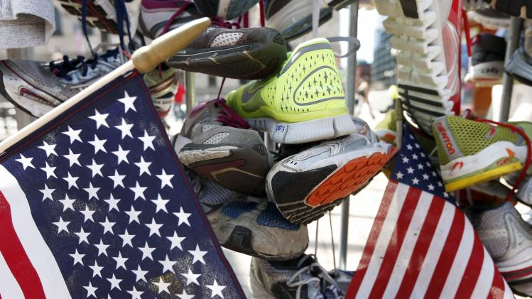 Running shoes hang from a barrier at a makeshift memorial in Copley Square on Boylston Street in Boston, Wednesday, April 24, 2013. Traffic was allowed to flow all the way down Boylston Street on Wednesday morning for the first time since two explosions on April 15. (AP Photo/Michael Dwyer)