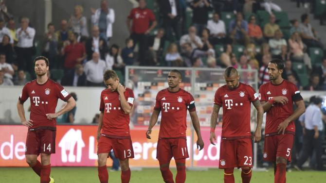 Bayern Munich players leave pitch dejected after being defeated by VfL Wolfsburg in German Supercup in Wolfsburg