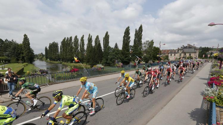 The pack of riders cross a canal in Baccarat during the161km eight stage of the Tour de France cycle race