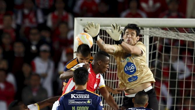 Yerry Mina of Colombia's Santa Fe heads the ball against goalkeeper Arnaldo Jimenez of Paraguay's Sportivo Luqueno during their Copa Sudamericana match at the Campin stadium in Bogota