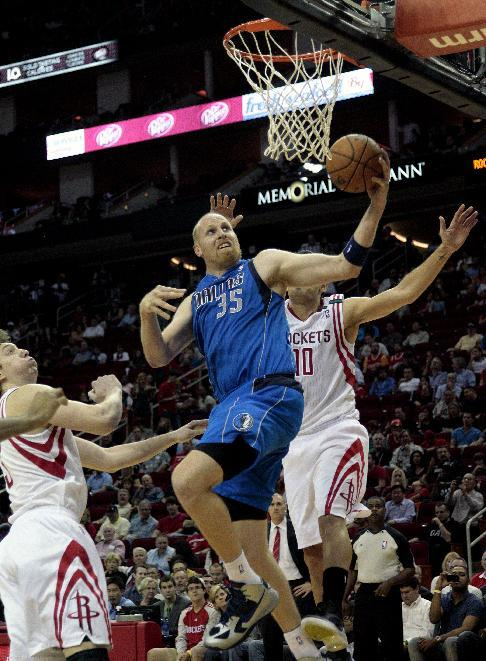 Dallas Mavericks' Chris Kaman (35) drives past Houston Rockets' Carlos Delfino (10) and Houston Rockets' Omer Asik (3) for a layup during the first half of an NBA basketball game, Saturday, Dec. 8, 2012, in Houston. (AP Photo/Bob Levey)