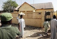 <p>A street vendor passes by a partially burnt police station in the Sheka neighbourhood in Kano on January 25, 2012. Gunmen opened fire at a primary school in the northern Nigerian city of Kano on Tuesday, injuring four teachers before fleeing on a stolen motorcycle, police said.</p>