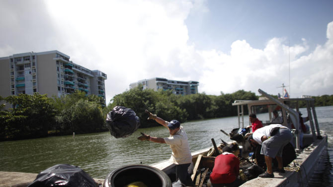 In this Oct. 26, 2013 photo, volunteers unload trash they removed from the San Juan Bay Estuary in San Juan, Puerto Rico. A plan to rescue this urban wetland, which is still a vital habitat and prime tarpon fishing ground despite the pollution, is a priority for the government, in part to bring more tourists and needed revenue to the capital of the U.S. island territory. (AP Photo/Ricardo Arduengo)