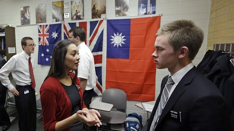 In this Jan. 8, 2013, photo, Mormon missionaries Mikaela Merrill, 19, center, and Harrison Surdu, right, practice their Mandarin Chinese during class at the Missionary Training Center in Provo, Utah. The Mormon churchís recent decision to lower the minimum age for missionaries has been greeted with† enthusiasm from many young members of the LDS church -- but especially young women. About half of all new applications to go on missions since the announcement have been from women, the church says. Prior to that, only 15 percent of missionaries were women. (AP Photo/Rick Bowmer)