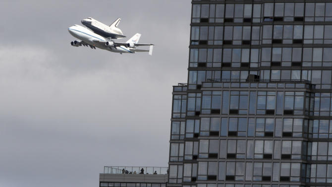 People watch from the balcony of a building as the space shuttleEnterprise, riding on the back of the NASA 747 Shuttle Carrier Aircraft, cruises over the Hudson river,  Friday, April 27, 2012 in New York. Enterprise is eventually going to make its new home in New York City at the Intrepid Sea, Air and Space Museum.  (AP Photo/Mary Altaffer)