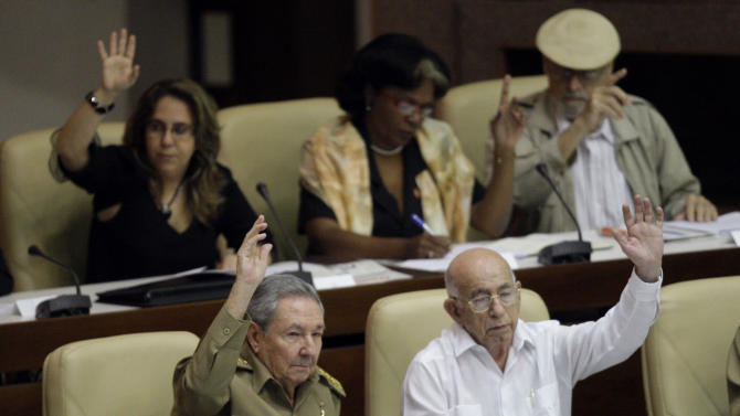 Cuba's President Raul Castro, bottom left, and Vice President Jose Ramon Machado Ventura, bottom right, raise their hands to vote on the 2013 budget during a session by the National Assembly in Havana, Cuba, Thursday, Dec. 13, 2012. The session is one of the National Assembly's twice-yearly gatherings. (AP Photo/Ismael Francisco, Cubadebate)