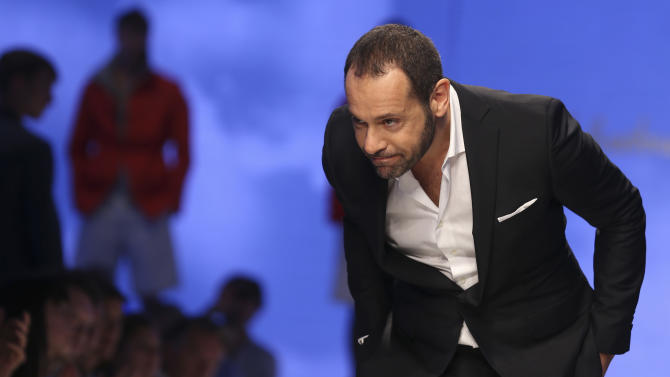 Creative director Massimiliano Giornetti acknowledges the applause of the audience at the end of the Salvatore Ferragamo men's Spring-Summer 2014 fashion show, part of the Milan Fashion Week, unveiled in Milan, Italy, Sunday, June 23, 2013. (AP Photo/Luca Bruno)