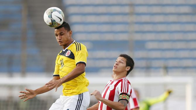 Colombia's Brayan Rovira Ferreira heads the ball under pressure from Paraguay's Juan Danilo Santacruz during their match for the final round of the South American Under-20 Championship in Montevideo