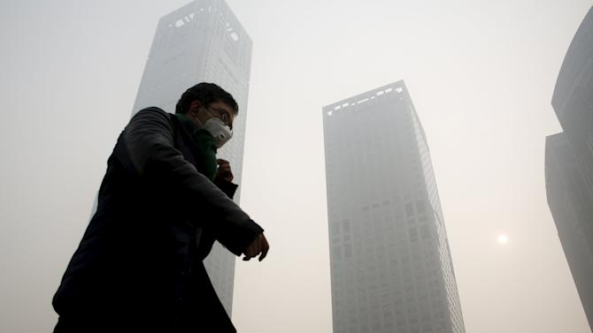A man wearing a mask makes his way at a financial district during a heavily polluted day in Beijing