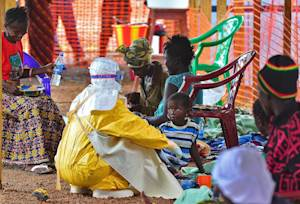 An MSF medical worker feeds an Ebola child victim at …
