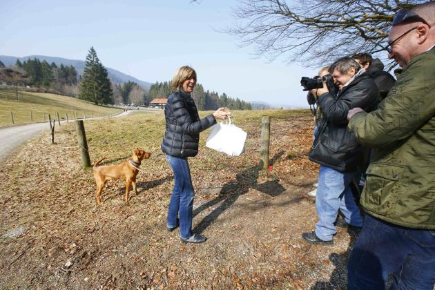 A woman from a local beer garden brings sausages in buns on behalf of Hoeness, resigned president and chairman of Bayern Munich, to journalists standing on public ground near his house in the Bavarian