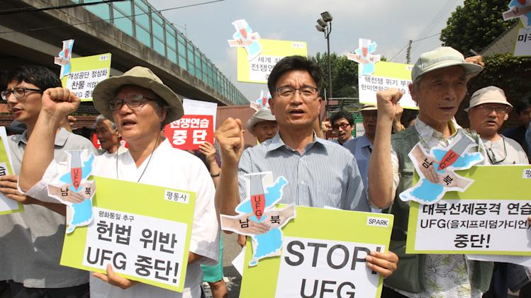 Protesters shout slogans during a rally against South Korea and U.S. joint military exercise Ulchi Freedom Guardian in front of Yongsan U.S. Army headquarters in Seoul, South Korea, Monday, Aug. 19, 2013. South Korea and the United States are conducting annual military drills that North Korea usually says are a rehearsal for invasion. Korean letters on the boards read: Stop Unchi Freedom Guardian Exercise. (AP Photo/Ahn Young-joon)