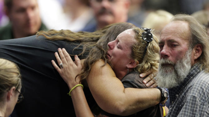 Mourners embrace during a memorial service Monday, July 1, 2013, in Prescott, Ariz., honoring the 19 firefighters killed battling a wildfire near Yarnell, Ariz., Sunday. The elite crew of firefighters was overtaken by the out-of-control blaze as they tried to protect themselves from the flames under fire-resistant shields. (AP Photo/Chris Carlson)