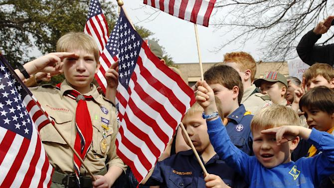 "FILE - In this Feb. 6, 2013 file photo, from left, Joshua Kusterer, 12, Nach Mitschke, 6, and Wyatt Mitschke, 4, salute as they recite the pledge of allegiance during the ""Save Our Scouts"" prayer vigil and rally against allowing gays in the organization in front of the Boy Scouts of America National Headquarters in Dallas, Texas. Under pressure over its long-standing ban on gays, the BSA announced Friday, April 19, 2013, that it will submit a proposal to its National Council to lift the ban for youth members but continue to exclude gays as adult leaders. (AP Photo/Richard Rodriguez, File)"