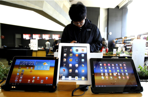 A student uses a mobile phone near the Samsung Electronics' new tablet Galaxy Tab 10.1 with Apple's white iPad on display, center, at the showroom in Seoul, South Korea, Monday, Oct. 3, 2011. If Samsung is to live up to the vaulting ambitions of its homeland and its top executives, many feel it must move beyond being a highly efficient imitator to creating products so original and seductive in function and design they become icons of consumer culture. (AP Photo/Lee Jin-man)