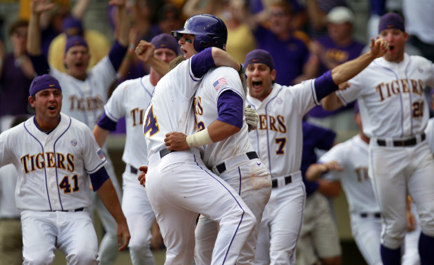 LSU infielder Tyler Moore (2), center, is mobbed by teammates after scoring on an RBI single by Mason Katz in the bottom of the 12th inning of an NCAA college baseball tournament super regional game against Stony Brook in Baton Rouge, La., Saturday, June 9, 2012. The game was a continuation of extra innings from Friday's rain postponement, and LSU won 5-4. (AP Photo/Gerald Herbert)