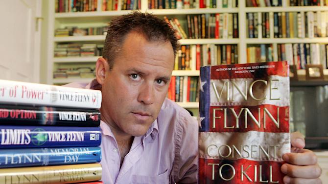 "FILE - In a Sept. 2, 2005 file photo is best-selling author Vince Flynn, who died just over a year ago, with copies of his books at his home in Edina, Minn. Like James Bond and other action heroes whose creators died, Flynn's terrorist-smashing character Mitch Rapp will live on in new books, Flynn's publisher confirms. Simon & Schuster has commissioned another thriller writer, Kyle Mills, to complete Flynn's unfinished last novel, ""The Survivor,"" and to write two more books in the Rapp series. (AP Photo/Jim Mone, File)"