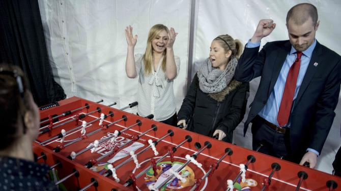 Sally Taylor-Isherwood, left, Jen McKee and Jordan Carroll celebrate a point during a fooseball or table soccer match at the FIFA Women's World Cup Trophy Tour launch at city hall  in Ottawa, Ontario, on Wednesday, April 1, 2015. (AP Photo/The Canadian Press, Justin Tang)