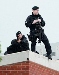 Armed police keep watch from the roof of the Lyric Theatre in Belfast, Northern Ireland. Queen Elizabeth II shook hands with former IRA commander Martin McGuinness on Wednesday in a landmark moment in the Northern Ireland peace process, Buckingham Palace said
