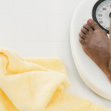 View-of-feet-of-a-woman-standing-on-weighing-scale_web
