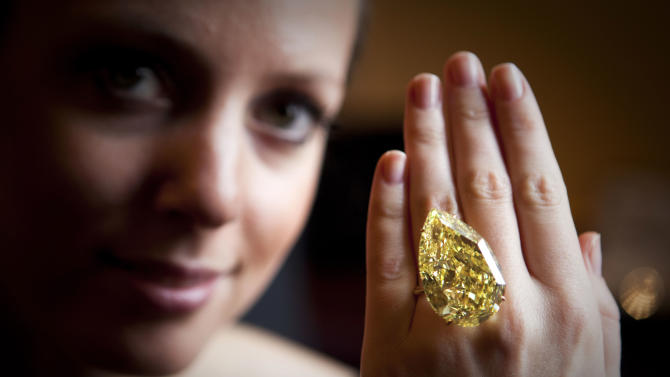 A model displays a 110.03 carats Sun-Drop Diamond described as fancy vivid yellow, the highest color grading by gemstone experts at a Sotheby's preview show in Geneva, Switzerland, Wednesday, Nov 9, 2011. Sotheby's says that the jewel is being sold by Cora International which discovered the diamond in South Africa last year. (AP Photo/Anja Niedringhaus)
