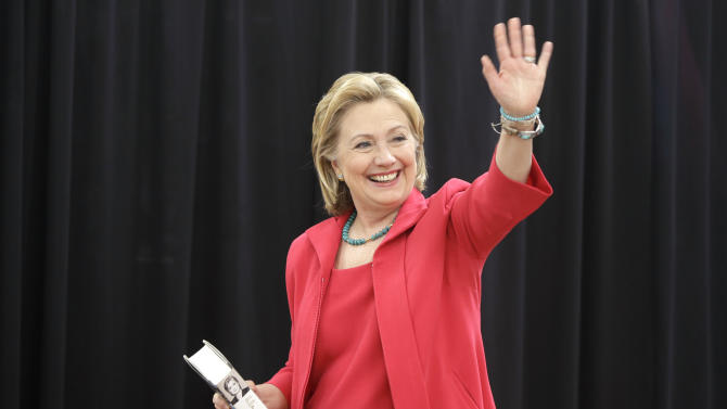 "Former Secretary of State Hillary Clinton waves as she arrives at a Little Rock, Ark., Wal-Mart store for a book signing event Friday, June 27, 2014. She carries a copy of her book ""Hard Choices"".(AP Photo/Danny Johnston)"