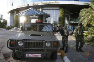 Thai soldiers stand in front of the National Broadcasting Services of Thailand television station in Bangkok