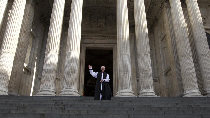 The new Archbishop of Canterbury Justin Welby waves outside St Paul's Cathedral as he poses for the media following his ceremony  known as the confirmation of election in London, Monday, Feb. 4, 2013. (AP Photo/Alastair Grant)
