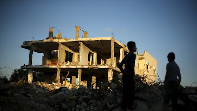 Palestinian boys play next to houses that witnesses said were destroyed during the 50-day war last summer, in the east of Gaza City