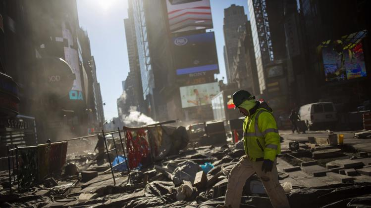 A worker walks while repairing the road at Times Square in New York