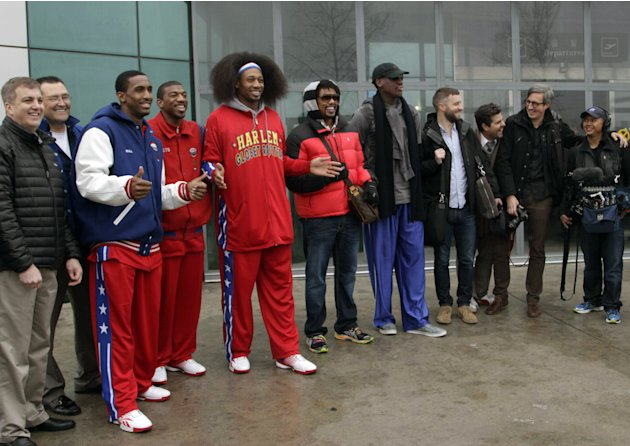 Flamboyant former NBA star Dennis Rodman, fifth from right, poses with three members of the Harlem Globetrotters basketball team, in red jerseys, and a production crew for the media upon arrival at Py