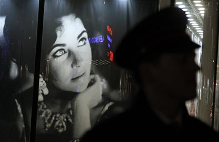 A security guard walks past an image of Elizabeth Taylor during an auction of the late actress' jewelry, clothing, art and memorabilia in New York