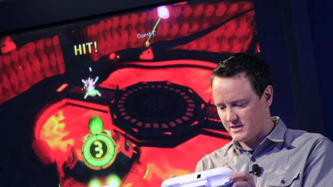 Nintendo's Bill Trinen demonstrates the Wii U GamePad, Thursday, Sept. 13, 2012 in New York. The gaming console will start at $300 and go on sale in the U.S. on Nov. 18, in time for the holidays, the company said Thursday. (AP Photo/Mark Lennihan)